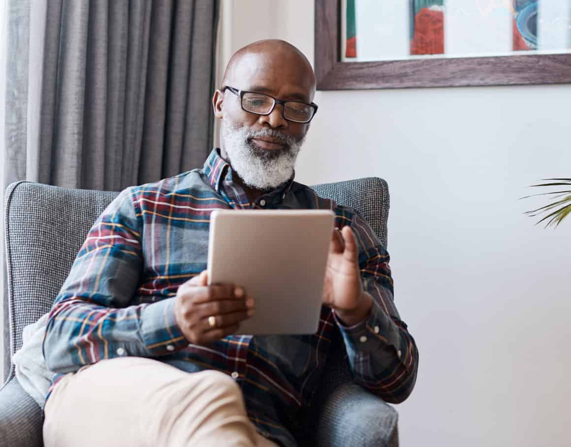 man sitting in chair with ipad